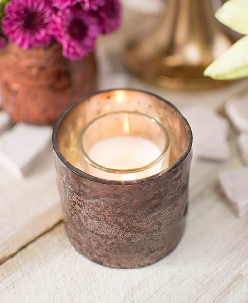 Add a romantic glow to your restaurant or wedding by arranging a votive candle in each mercury glass candle holder.