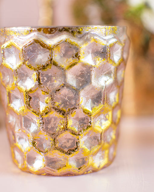 Standing 3.25 inches tall, each vessel is detailed with a honeycomb pattern accented with blush pink and gold colors.