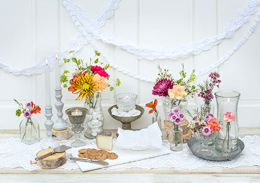 Dress your table in delicate vintage details with our clear glass heirloom compote. Fill the scene with a lace table runner, clear glass decor, antique grey compotes, a marble cheese paddle and floral accents.