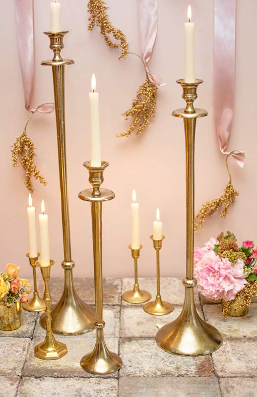 Style this candlestick with our other tall metal candlesticks and our brass candle holder collection. Fit taper and stick candles easily into these decorations and embellish the scene with gold toned berry sprigs attached to pink ribbons and mercury glass vases holding floral bouquets.