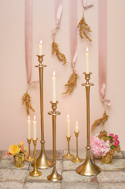 Decorate your wedding in grand elegance with our collection of antique gold colored metal candle holders. Complete the scene with brass candlesticks, vases with floral bouquets and ribbons displaying berry sprigs.