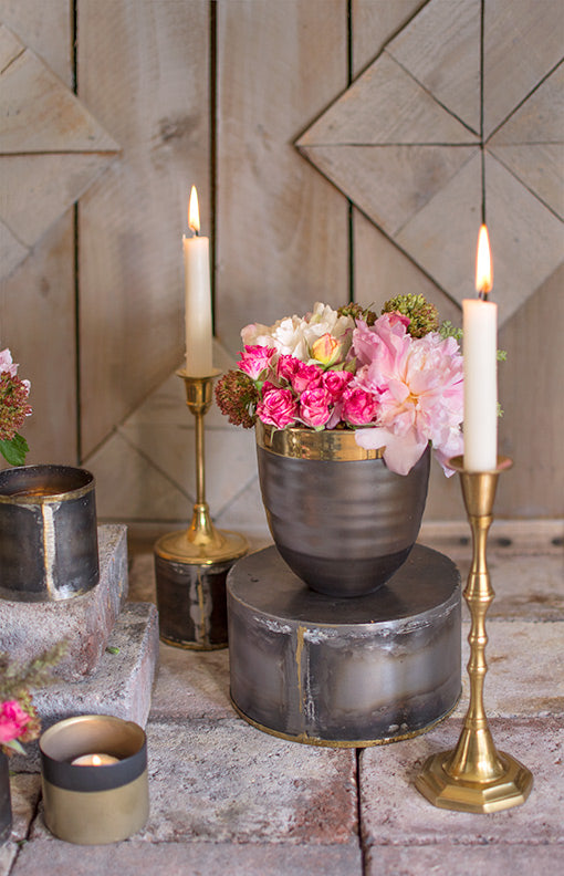 Use this vase as a pedestal for a ribbed planter pot. Style the scene with solid brass candlesticks, flowers and taper candles.
