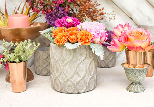 Fill this planter pot with flowers and sprigs for an enriching centerpiece in your wedding tablescape. Add our antique grey compote and copper colored candle holders to complement this design.