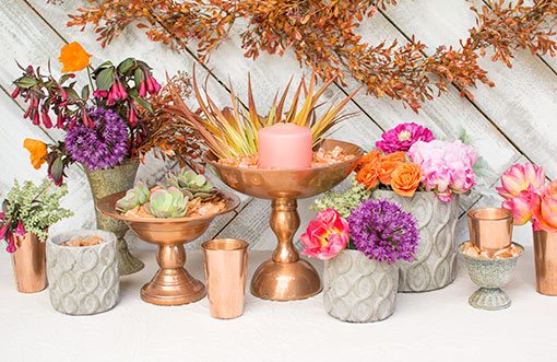 Fill your table with concrete accents and glowing copper colored decor! Detail these pieces with succulents, flowers and sprigs for a fresh garden display at your event.