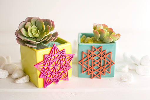 Tape or glue these laser cut ornaments to neon colored vases and surround with white rock table scatter. Fill each vase with sand or green rock vase filler and succulents.