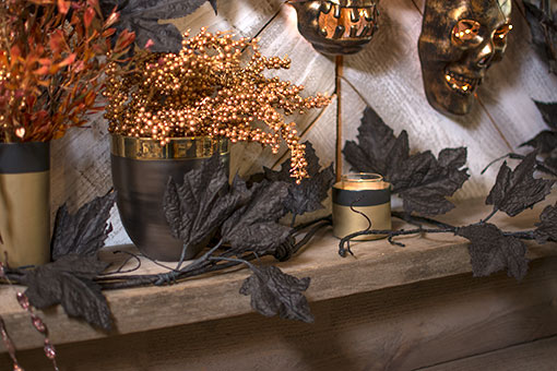 Weave this garland between planter pots and candle holders for a creeping vine design. Accent the scene with a gold toned berry sprig, copper colored spray and masks devilishly smiling with fairy lights.