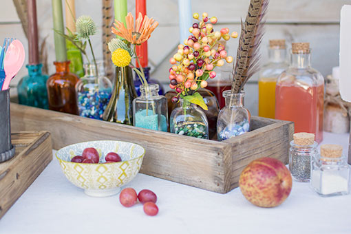 Create an eye-catching centerpiece with a wood vase containing glass bottle bud vases filled with fine grain filler, berry sprigs, decorative feathers, colorful candles and filler flowers.