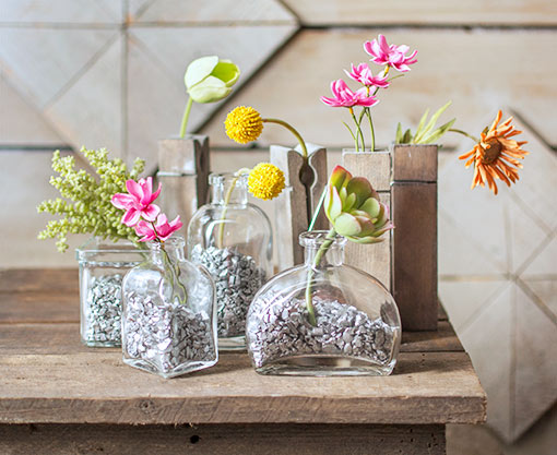 Fill bud vases with silver vase filler and a variety of florals and greens for a complete scene.