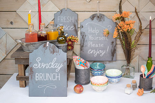 Dress up brunch buffets with florals, tidbit bowls, galvanized vases, colorful utensils, glass bottles and chalkboard signs.