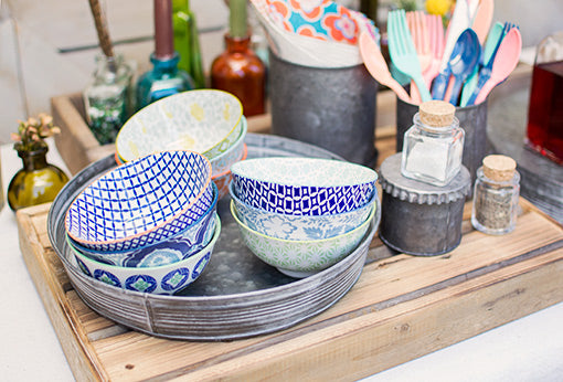 Galvanized serving trays and charming glass bottles accessorize these colorful ceramic luncheon bowls.