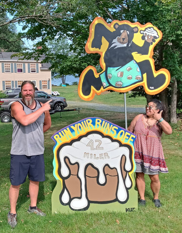 Alison and Charlie standing at the installation of the Bear and sticky buns painting for the Run your Buns Off 4.2 Miler in Bridgewater, Nh
