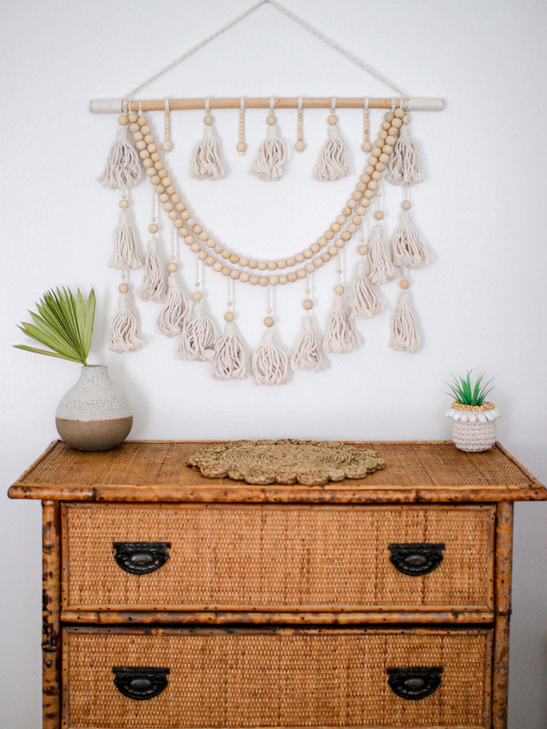beautiful bohemian wall hanging macrame above a rattan and bamboo dresser