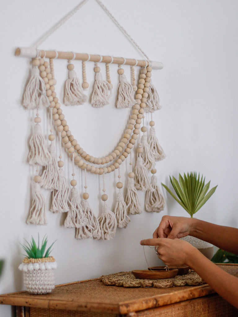 side view of a beautiful macrame wall hanging above a bamboo dresser with plants