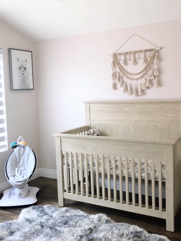 wall hanging macrame in nursery above the baby crib