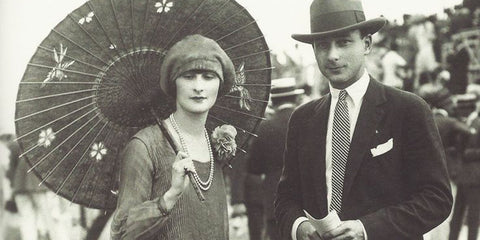 Man and woman in the 1920s outside. Man wearing hat and suit and woman wearing a dress hat and umberalla.