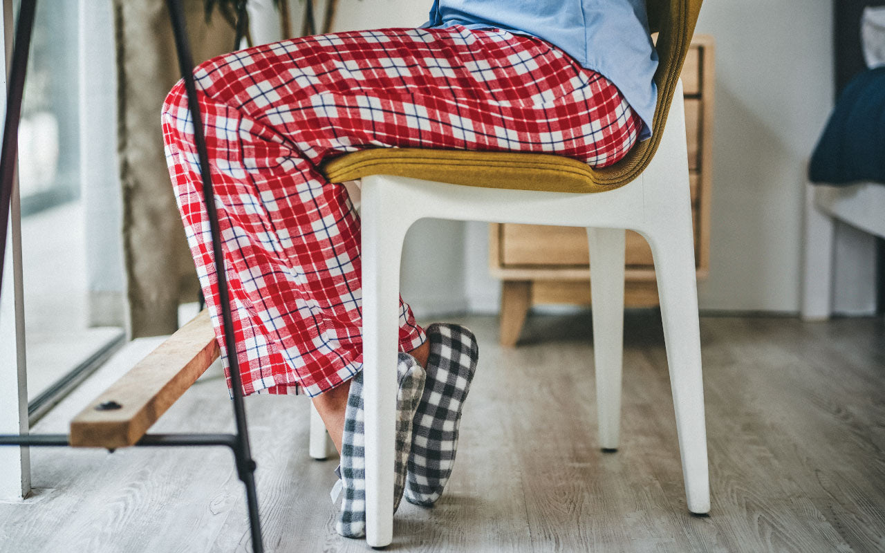 Woman sitting at her desk and wearing bright red patterned flannel pajamas and grey flannel slippers