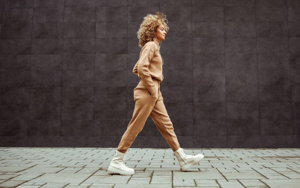 Woman walking in full brown sweat suit outfit with white combat boots while listening to music