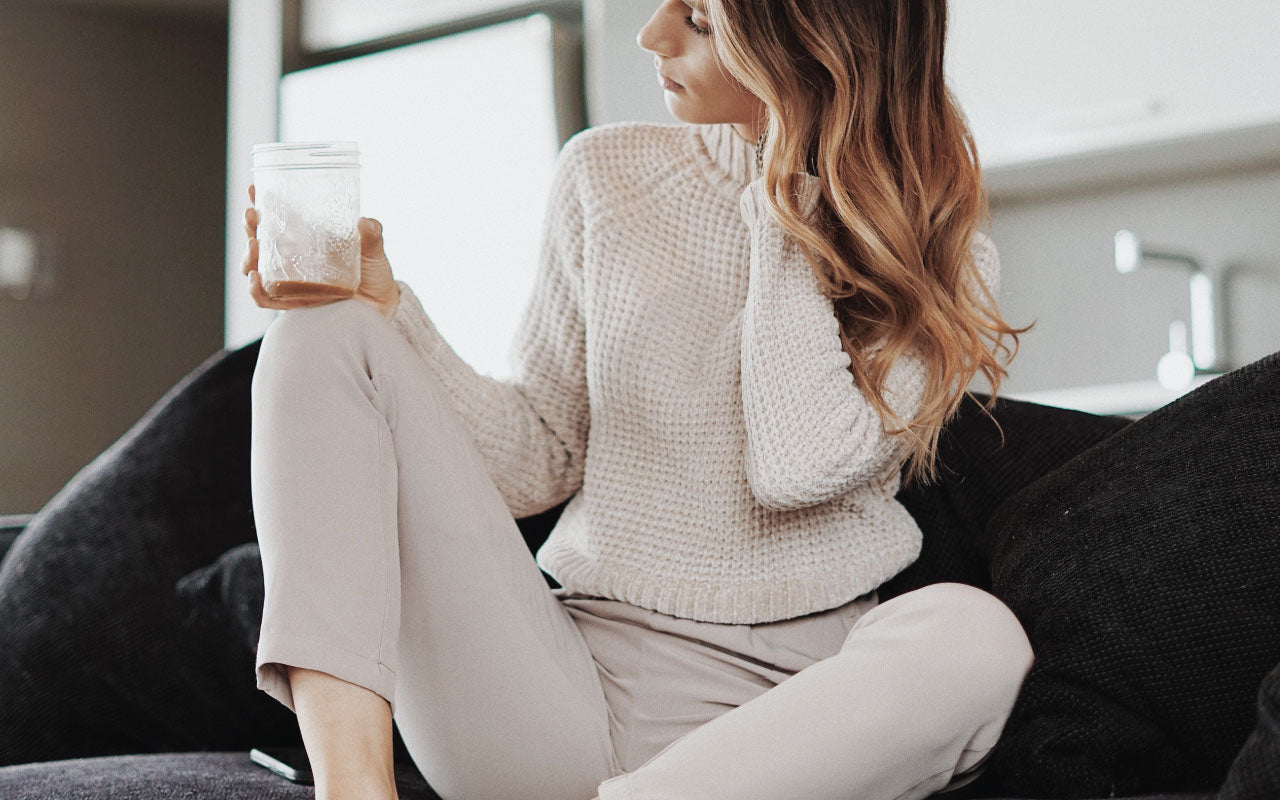 Woman wearing stylish beige sweater and sweatpants outfit sitting on her dark couch and holding a empty mason jar of coffee