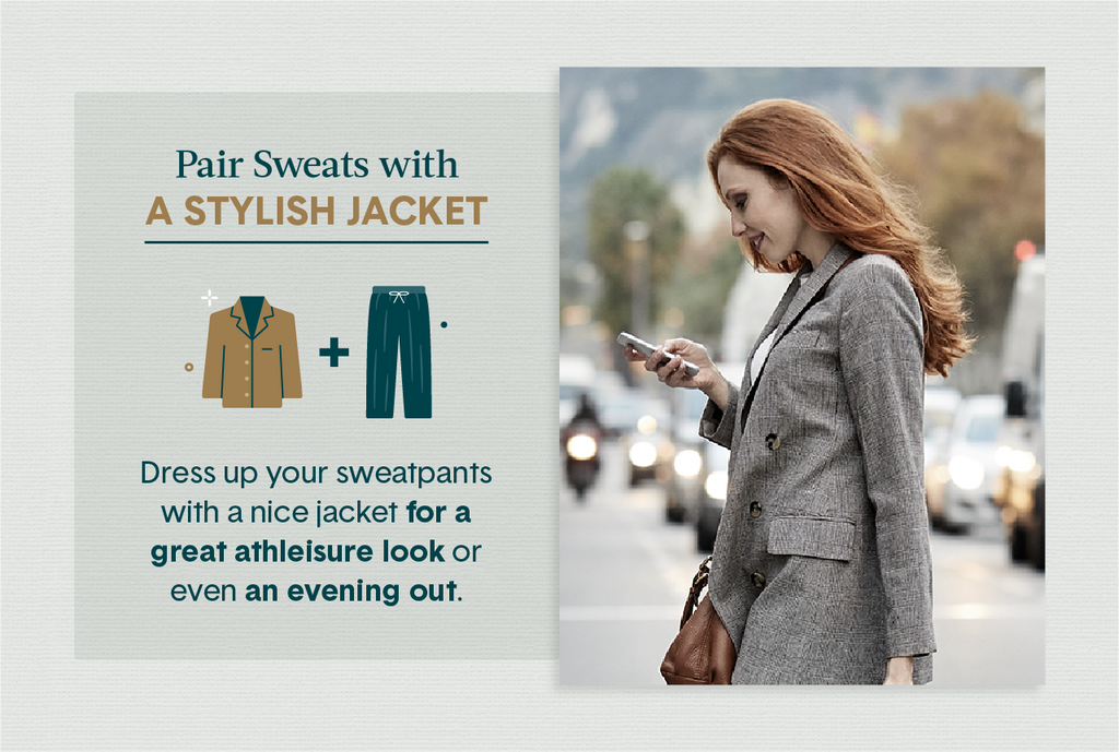 Redheaded woman wearing a heather grey blazer crossing a busy street and looking down at her phone
