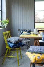 Colourful cushion covers at a yellow kitchen table