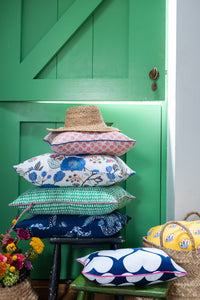 Colourful cushion arrangements with green door and baskets