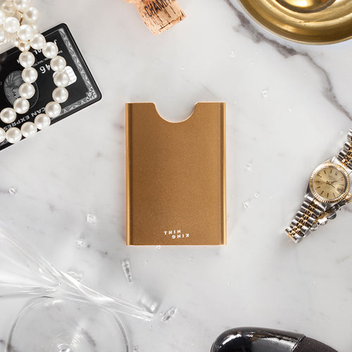 Champagne colour Thin King credit card case  with a black Amex