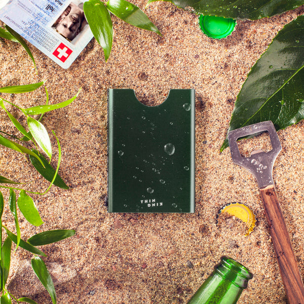 Bullitt green Thin King credit card case on a sandy beach