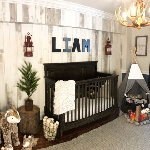 Camping themed nursery with custom wall name letters spelling out Liam.