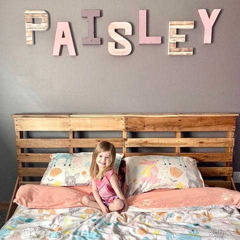 Adorable little girl in her big girl room with custom wall name letters spelling out her name Paisley.