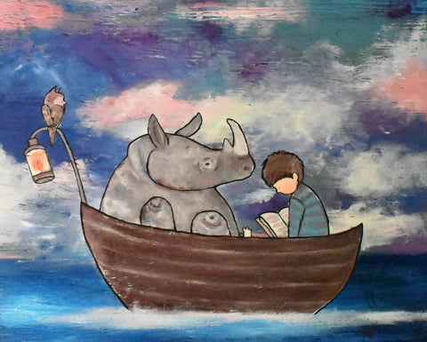 Kids wall art showcasing a rhino and a little boy on a boy in the ocean for art decor for toddler room ideas.