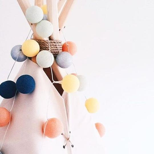 Fun colorful string lighting draped around the top of a canvas tent for boys playroom decor.