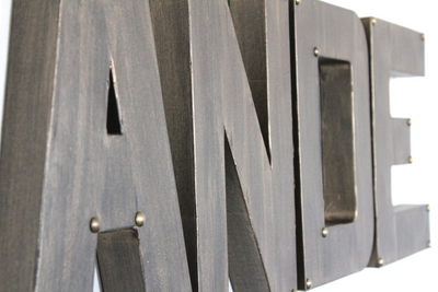 Industrial letters in bronze spelling out Ande with bronze metal studs on the corners.