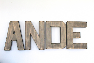 Industrial letters spelling out the name Ande with bronze metal studs on the corner for rustic nurseries and industrial nursery decor.