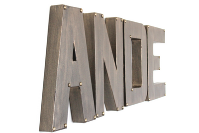Bronze letters spelling out Ande with bronze studs on the corners.