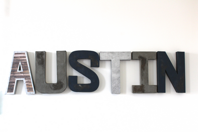Rustic woodland nursery letters spelling out Austin in silvers, navy, and browns.