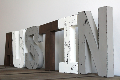 Rustic nursery name letters spelling out Austin in brown, white, and light gray colors.