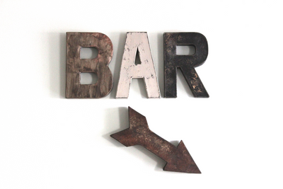 Bar sign in brown, gray, and black with a wooden distressed arrow.
