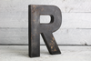 Black distressed letter R.
