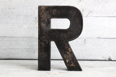 black free standing letter R in a distressed and weathered wood finish.