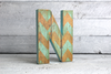 boho style letter N featuring a blue and brown chevron pattern on the front.