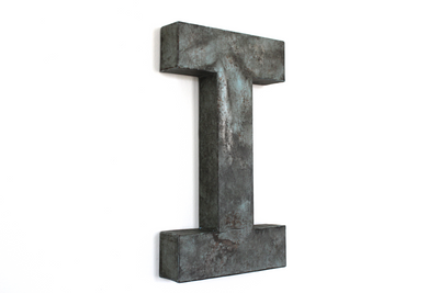 distressed wooden letter I with a rusty finish in blue green.