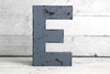 blue letter on a wooden pallet in a distressed vintage style with black distressing