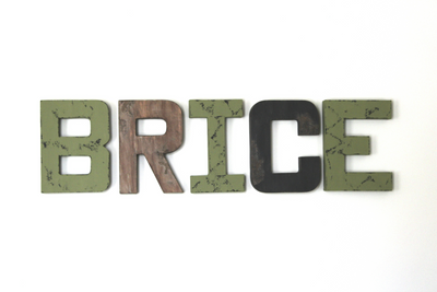 Wall name letters spelling out Brice in green, brown, and black letters for a forest themed nursery.