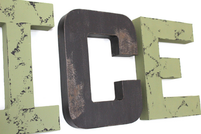 Distressed rustic letters in green and black for a forest themed nursery.