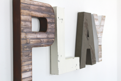 Play sign for playroom decor in browns, grey, and whites.