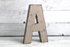 "Distressed gray ""wooden"" letter freestanding in a wooden background"