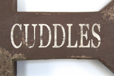 Faux Wooden arrow with the word cuddles on arrow in a distressed finish.