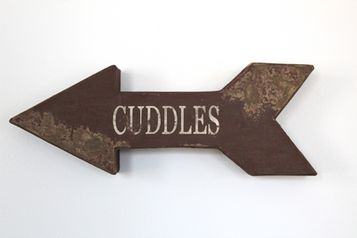 Faux Wooden arrow pointing to the left with the word cuddles in a distressed finish.