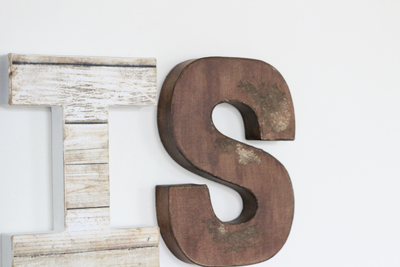 Distressed letters in brown and beige.
