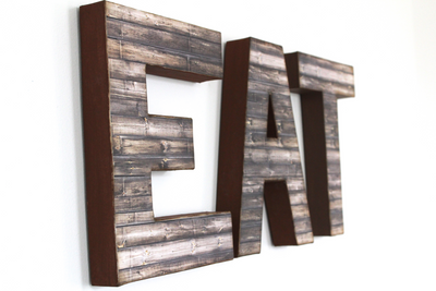 Rustic farmhouse EAT letters hung on wall for kitchen decor.